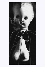 surrealist sculpture - doll head on wireframe with a pair of breasts ensconced